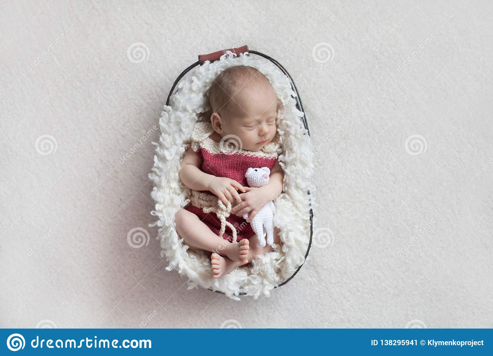 A newborn baby sleeps in a basket in a pink body with a small toy.