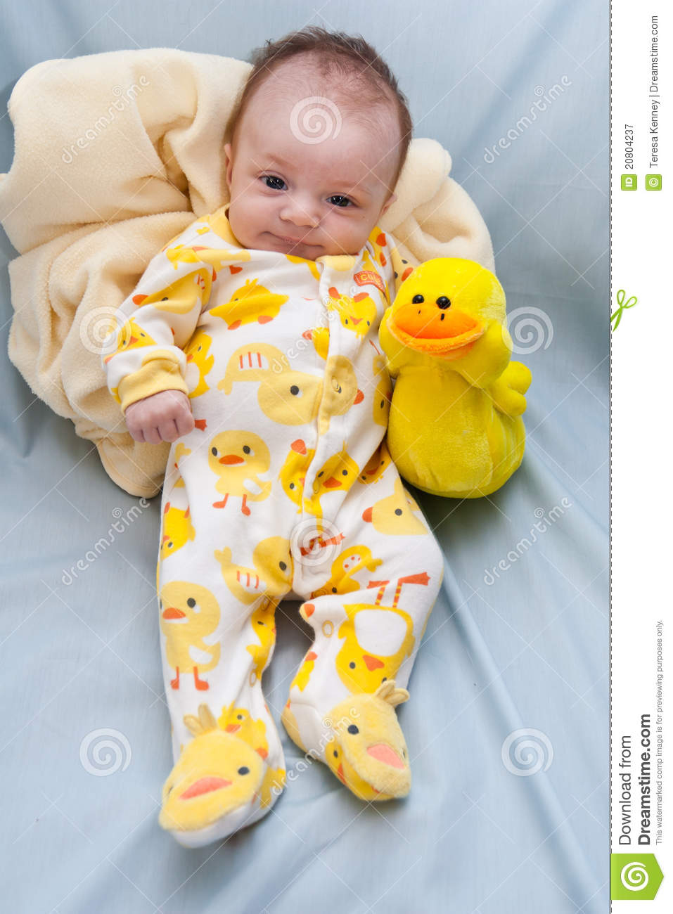 ... ducks and holding a stuffed duck toy. Background is light blue fabric