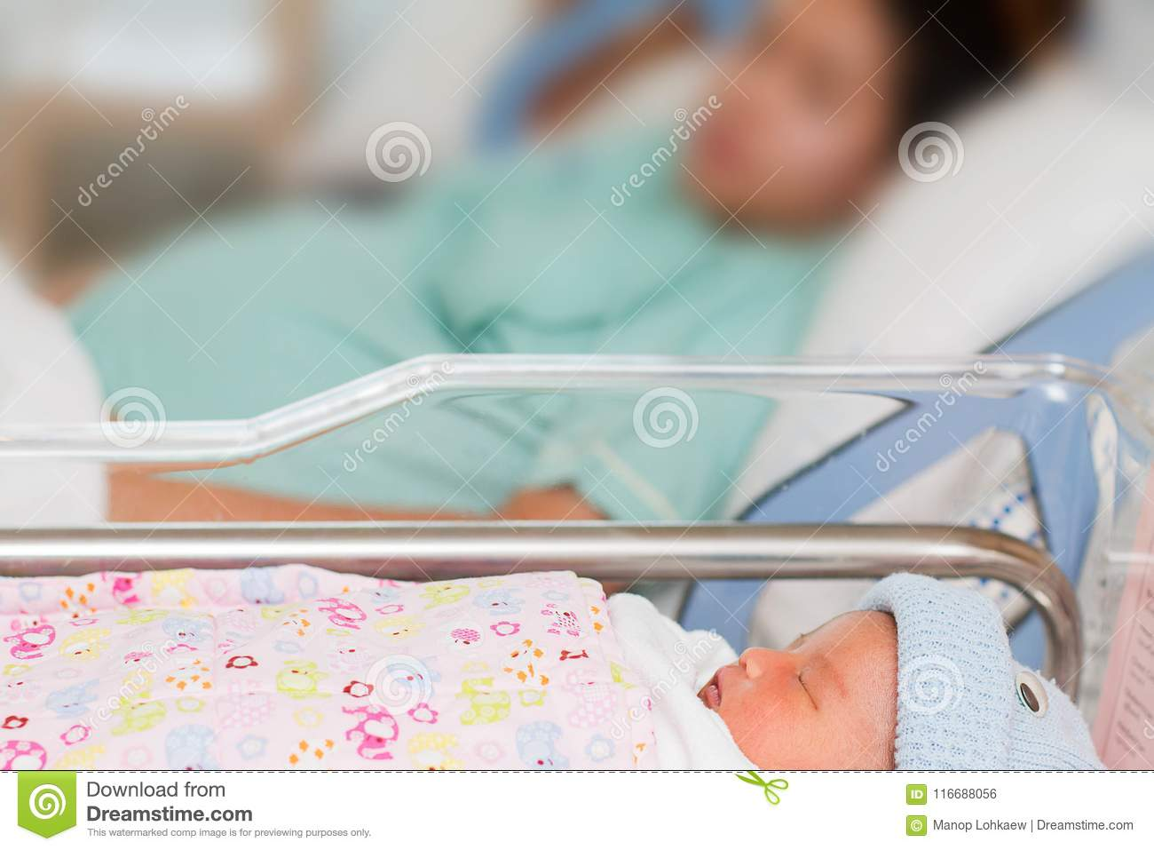 Newborn infant baby girl sleeping on blurred mother in ho