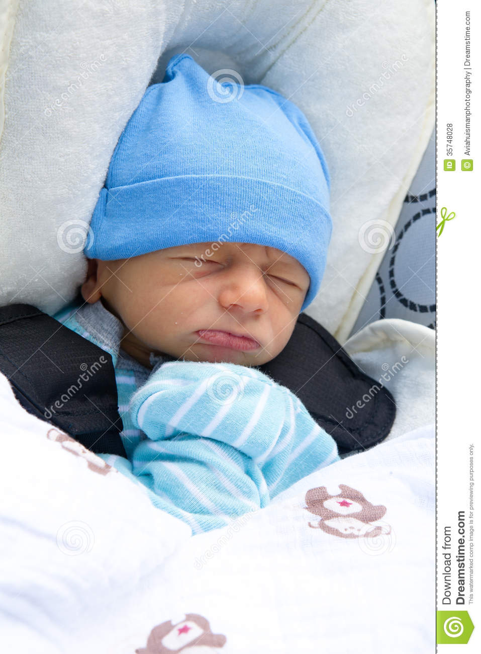 A newborn baby napping in a stroller wearing a blue hat and mittens. a970cdf46