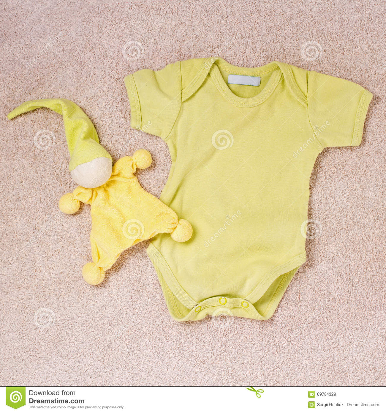 Yellow newborn button up onesie and toy clown with night hat on top of soft  pink carpeting a160711e0fd