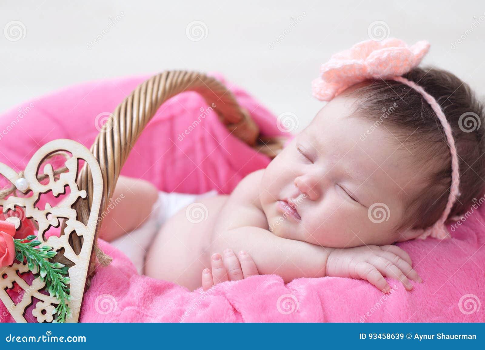 newborn sleeping in basket, baby girl lying in pink blanket, cute