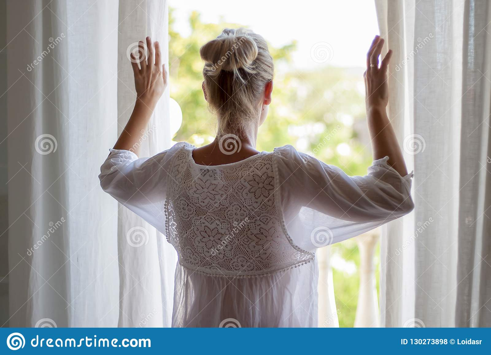 Woman looking out the window in pijama.