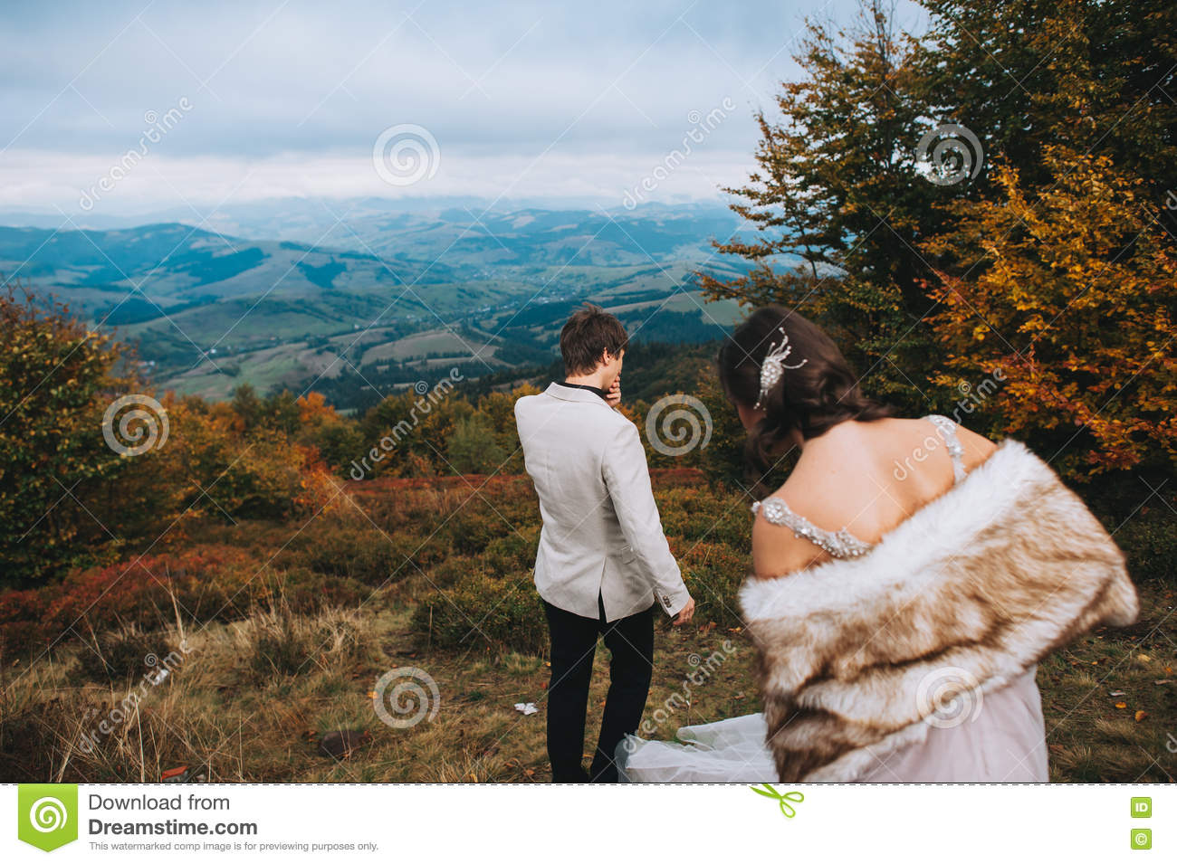 Newly married couple posing in the mountains