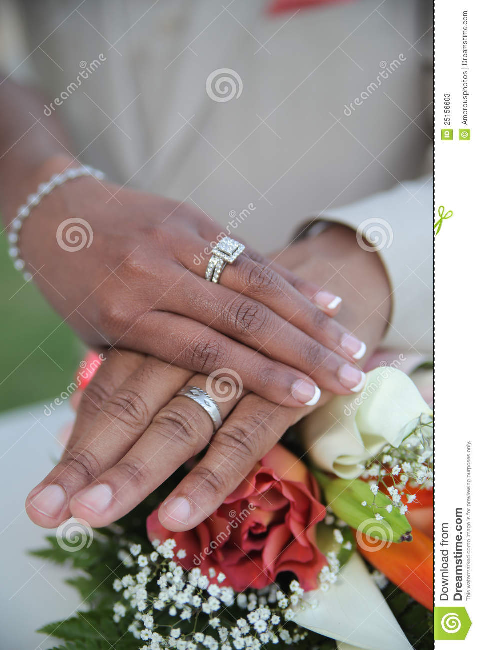 Newlywed couple holding hands over top of wedding flower bouquet