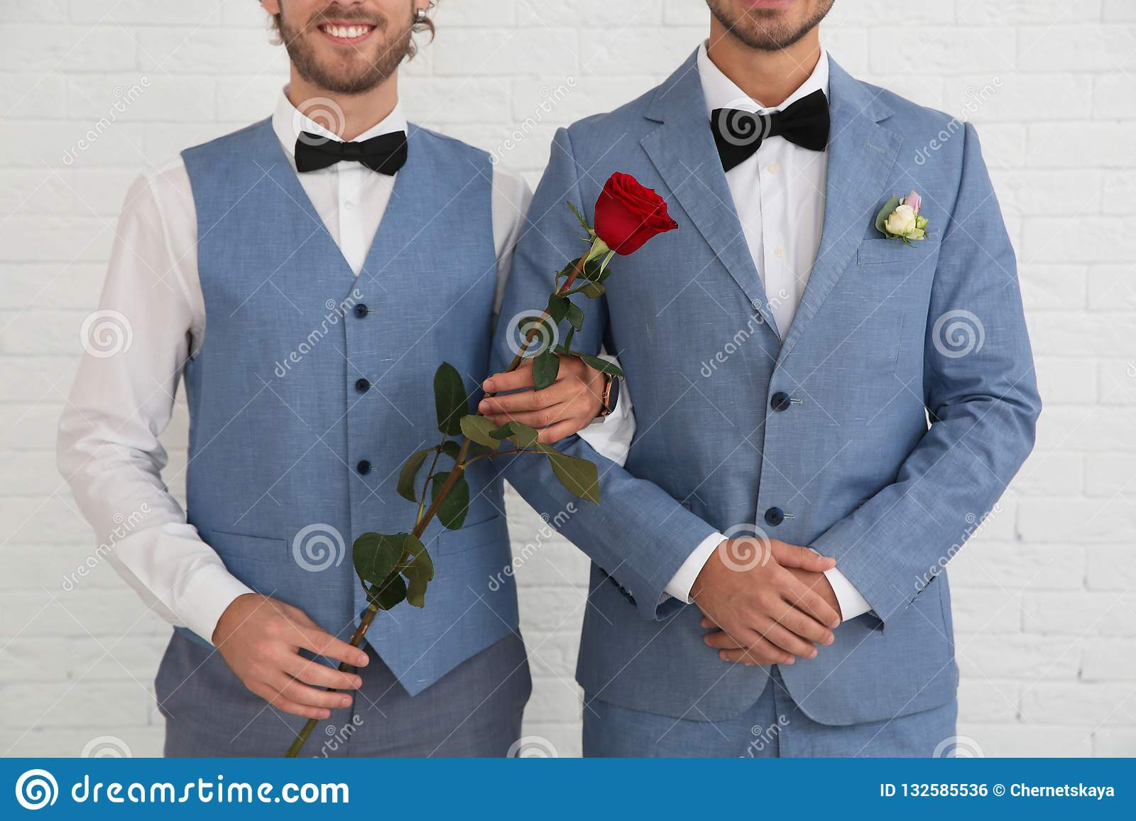 Newlywed gay couple with rose near white wall