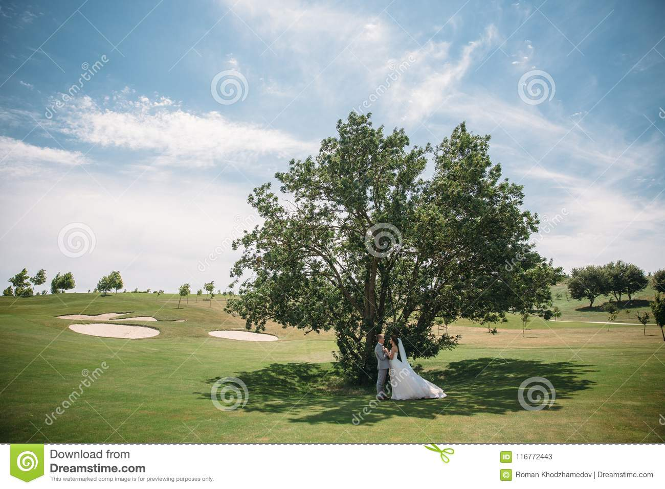 Newlyweds on a green tree background in a golf club on a wedding day. The groom in a business suit is gray and the bride