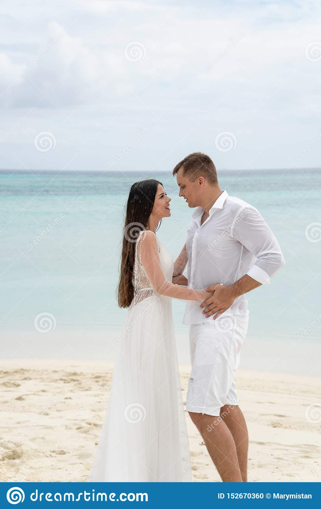 Newlyweds are hugging on a gorgeous beach with white sand and turquoise water