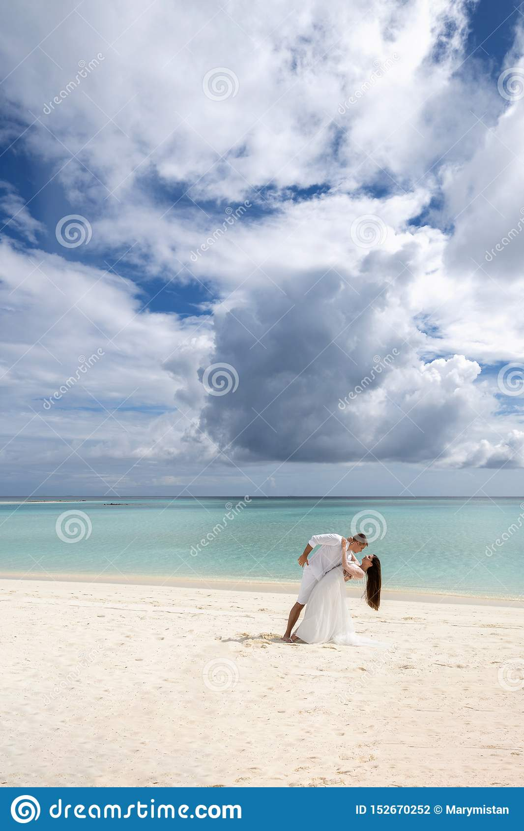 Newlyweds are passionately dancing on a gorgeous beach with white sand and turquoise water