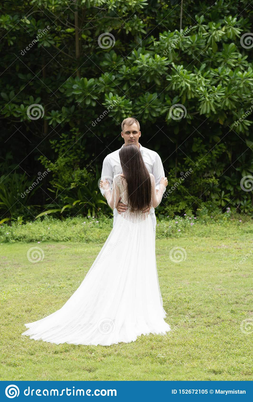 Newlyweds stand on a green lawn against the backdrop of a tropical forest