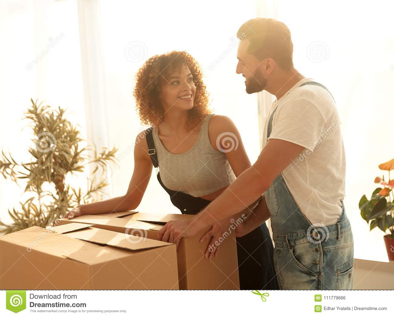 Newlyweds unpack boxes in a new apartment.