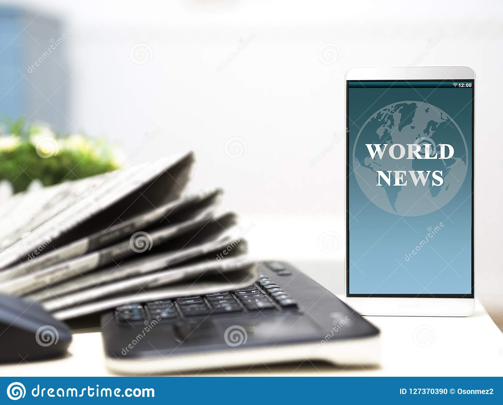News article from the world on your smartphone screen. newspapers with keyboard on table
