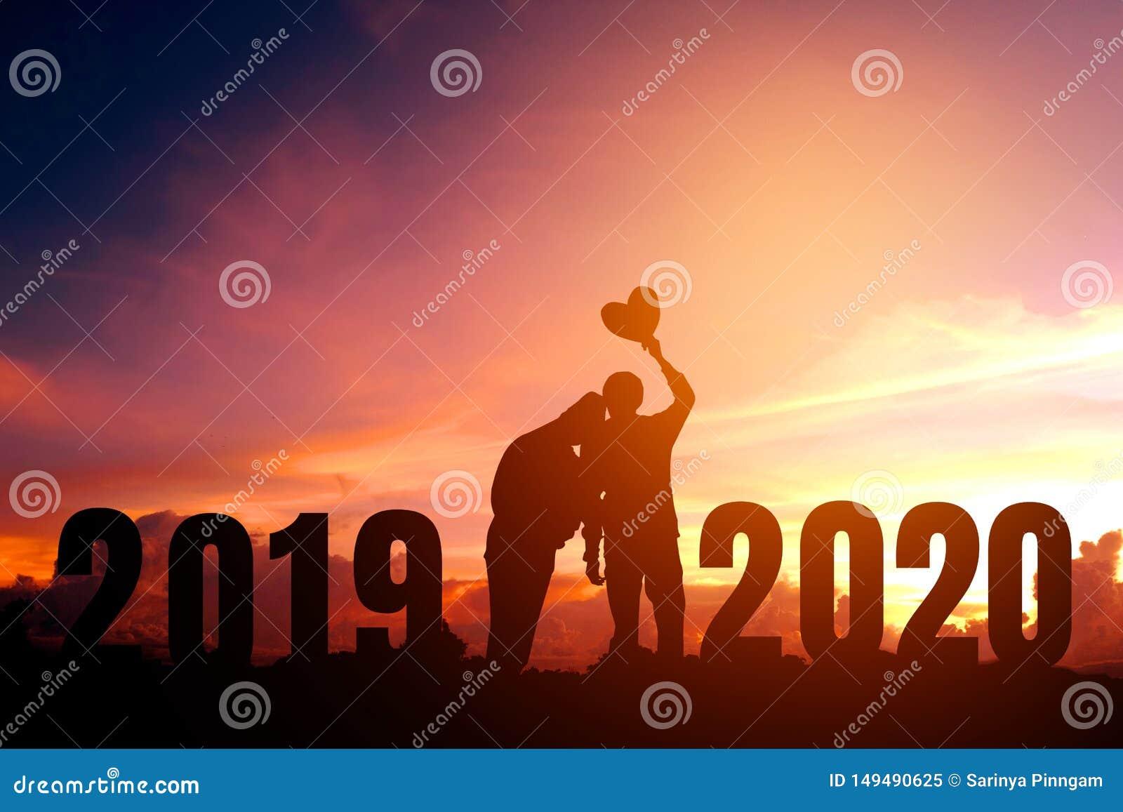 Newyear 2020 silhouettieren die jungen Paare, die f?r romantisches Konzept des neuen Jahres gl?cklich sind