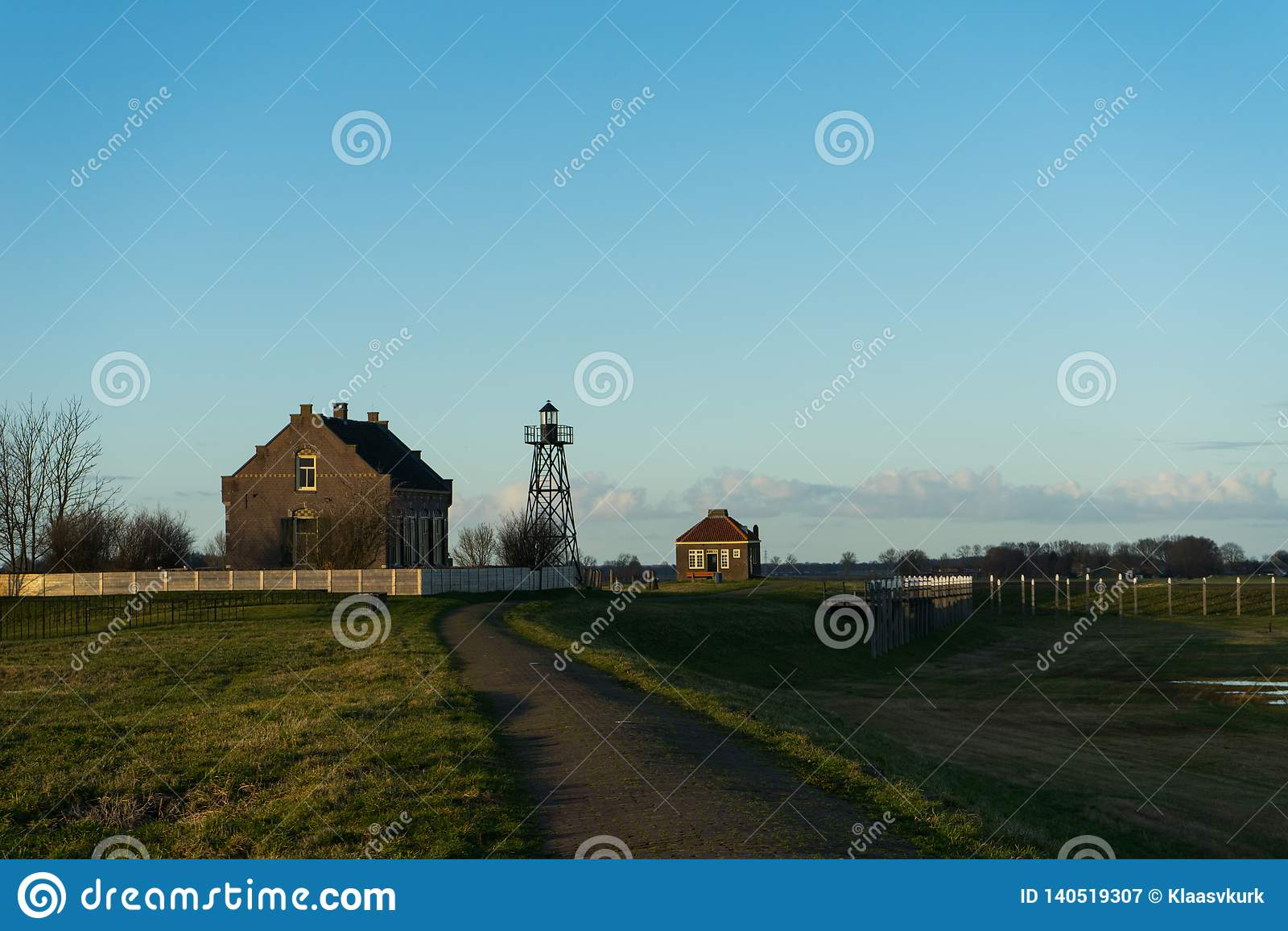Nex da torre do farol do metal ao céu azul do trajeto principal do landhouse nenhumas nuvens Grama verde