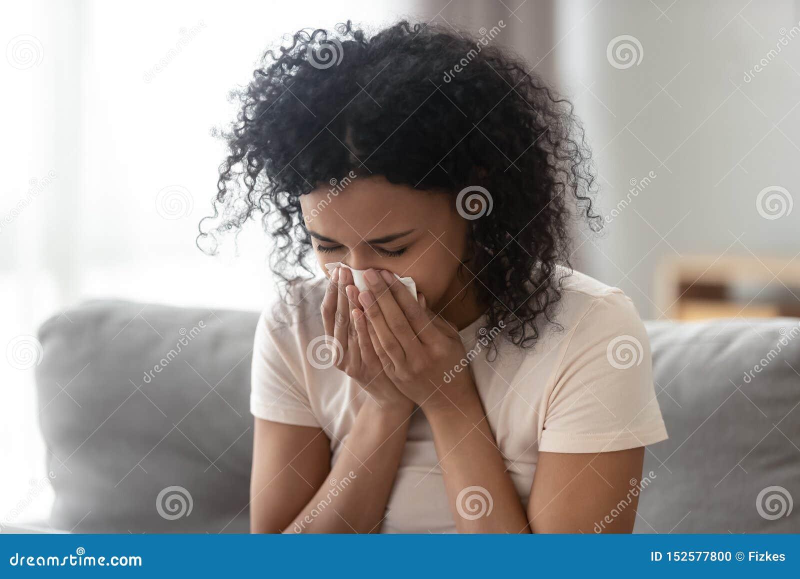 Nez de soufflement africain allergique malade de femme dans le tissu à la maison