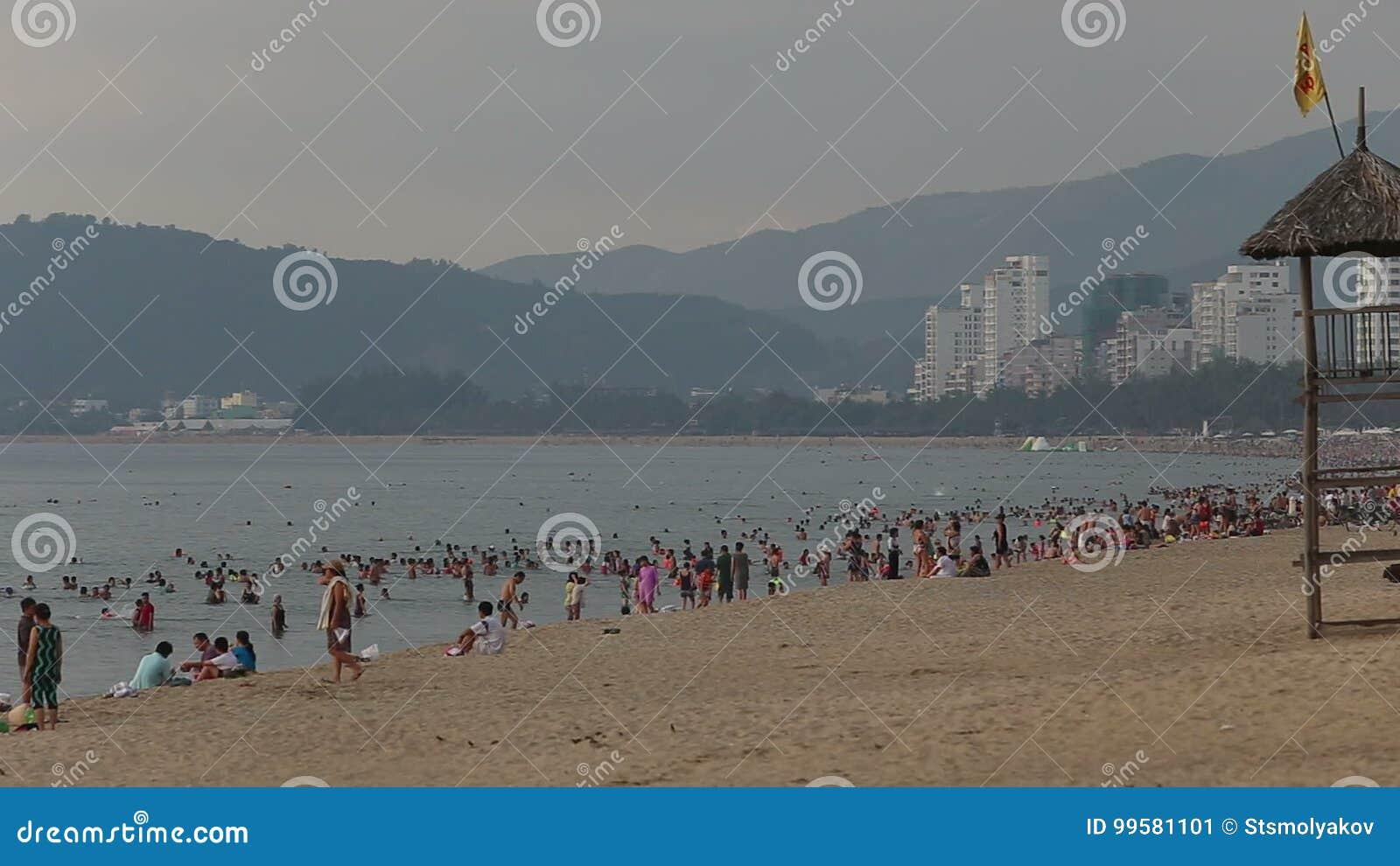 people swim burn on city beach in VietNam at dawn
