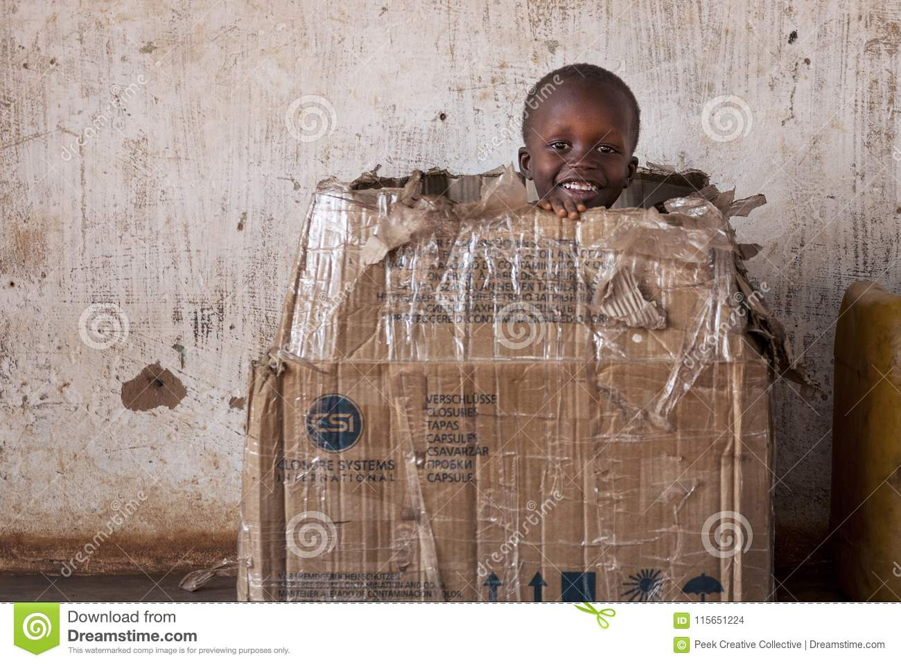 Portrait of a young boy playing in a card box in the town of Nhacra in Guinea Bissau