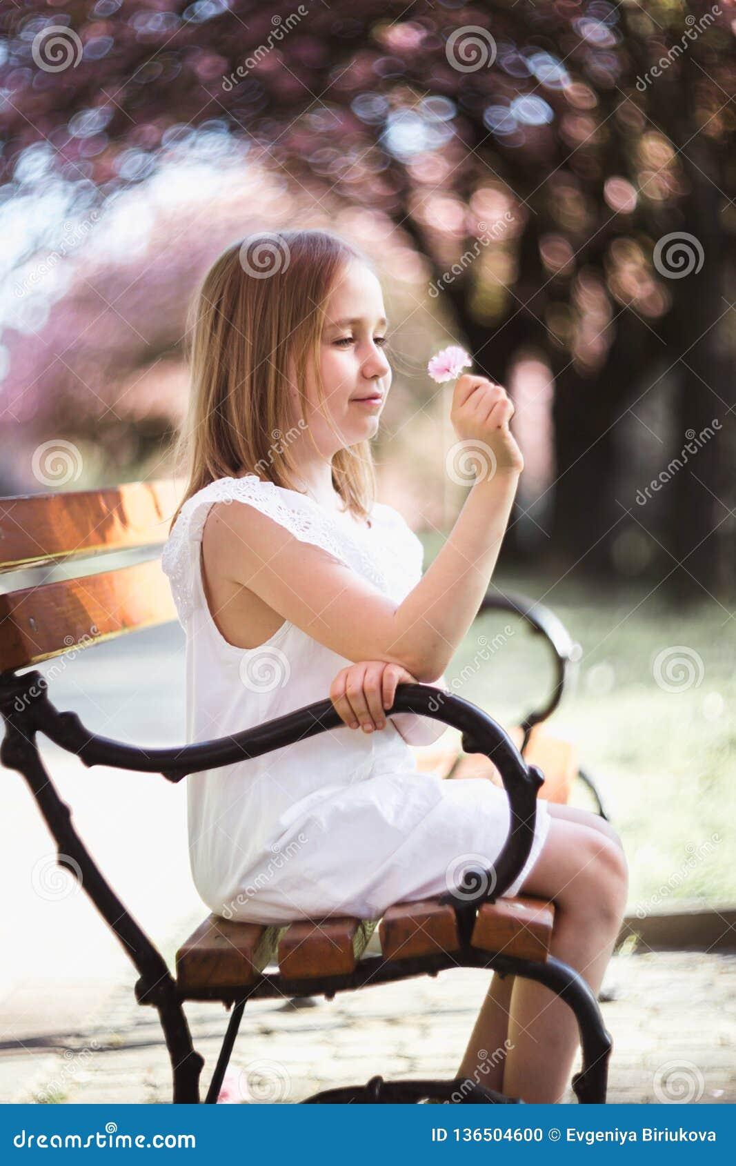 Niña adorable en el vestido blanco en jardín rosado floreciente en día de primavera hermoso