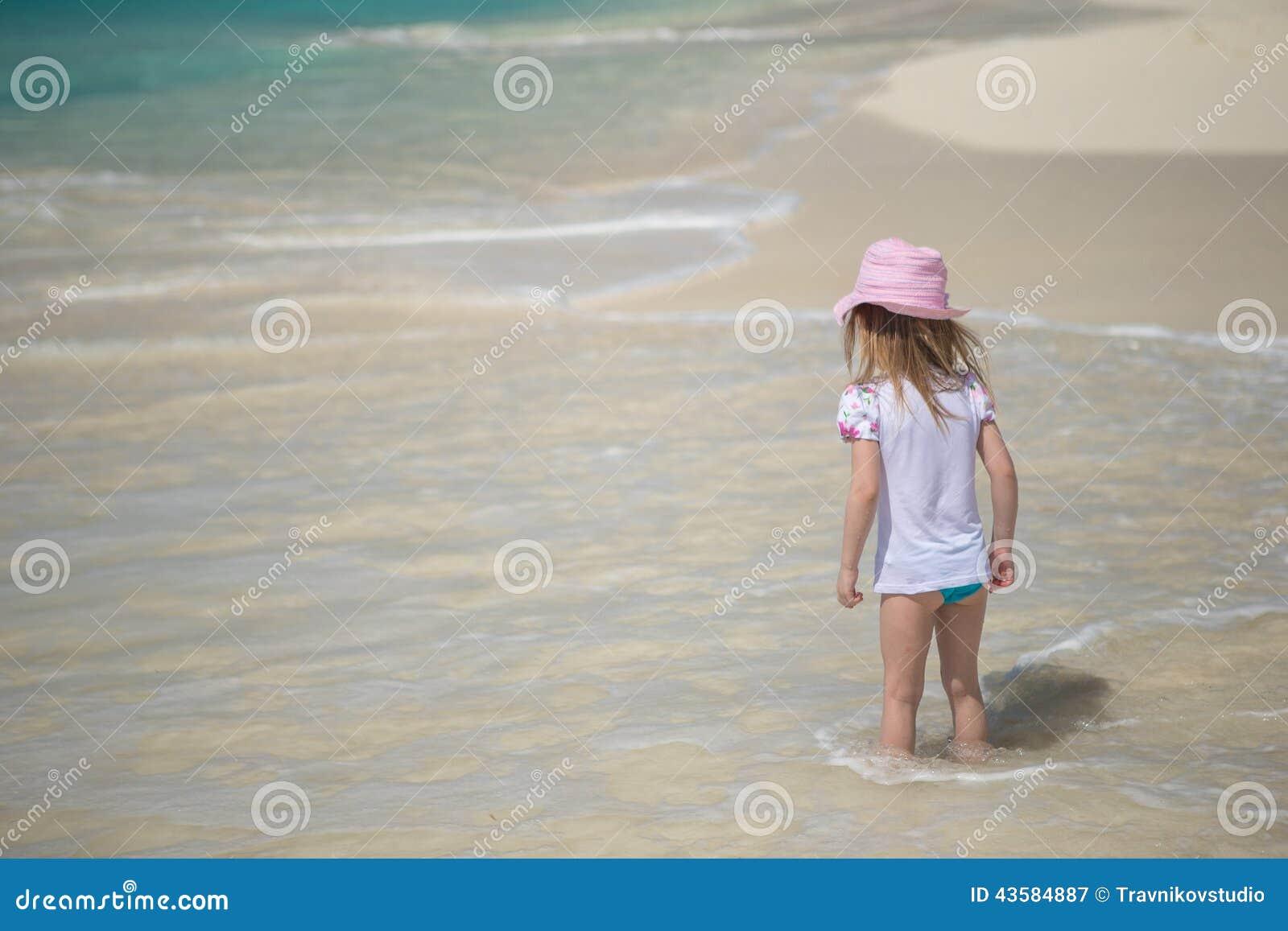 Niña adorable que juega en agua poco profunda en