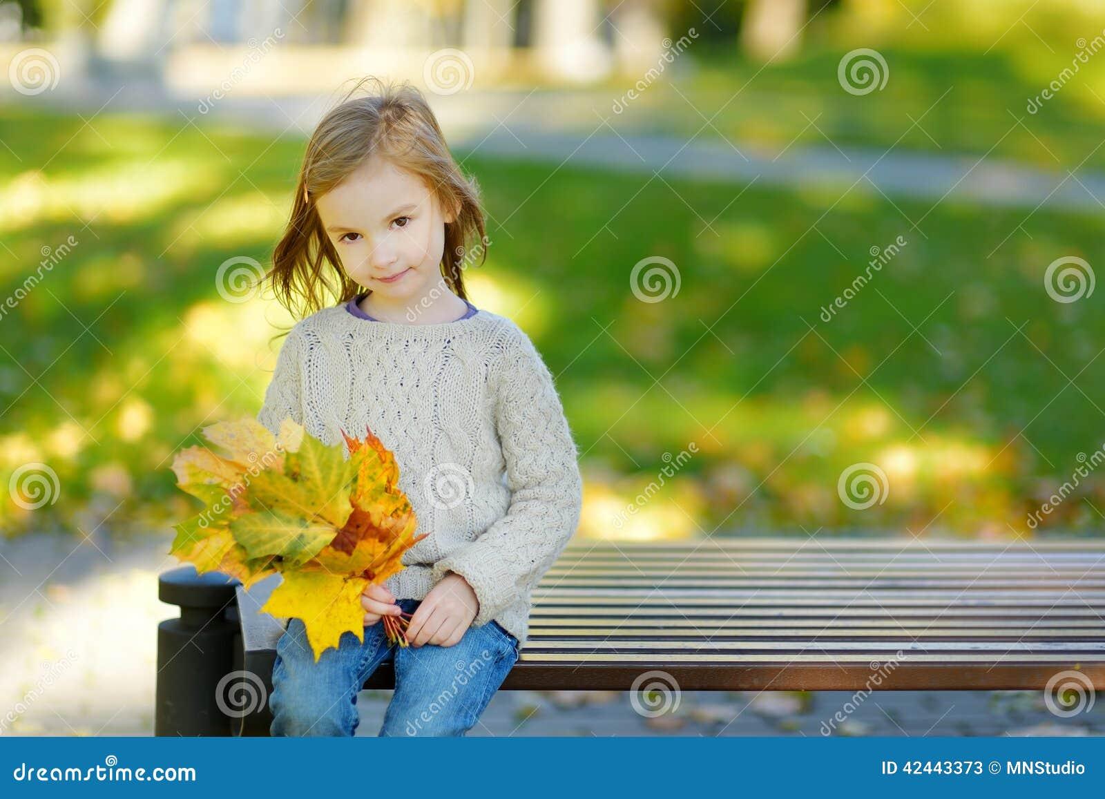 Niña adorable que se divierte el día del otoño