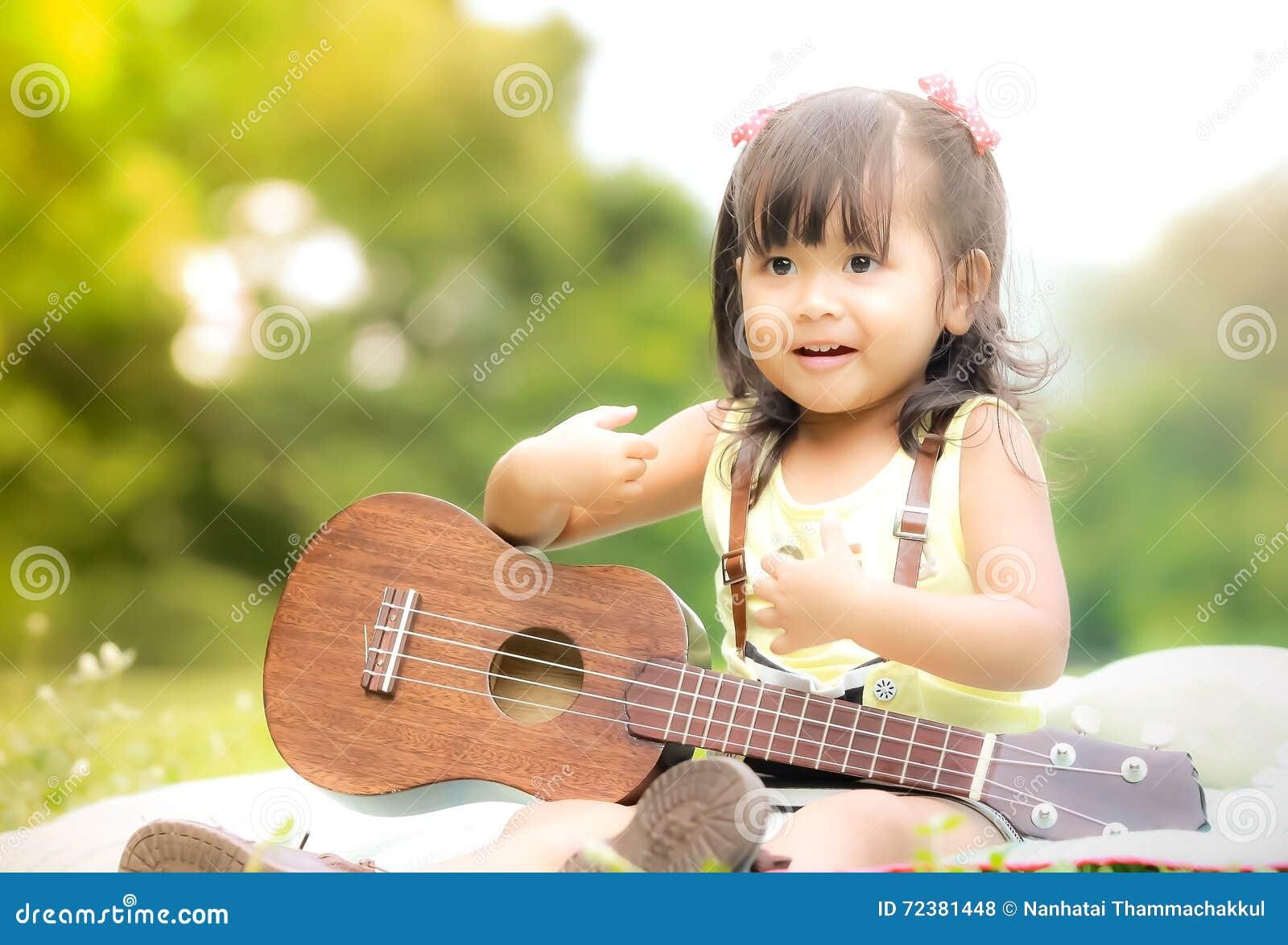Niña asiática que se sienta en hierba y el ukelele del juego en jardín