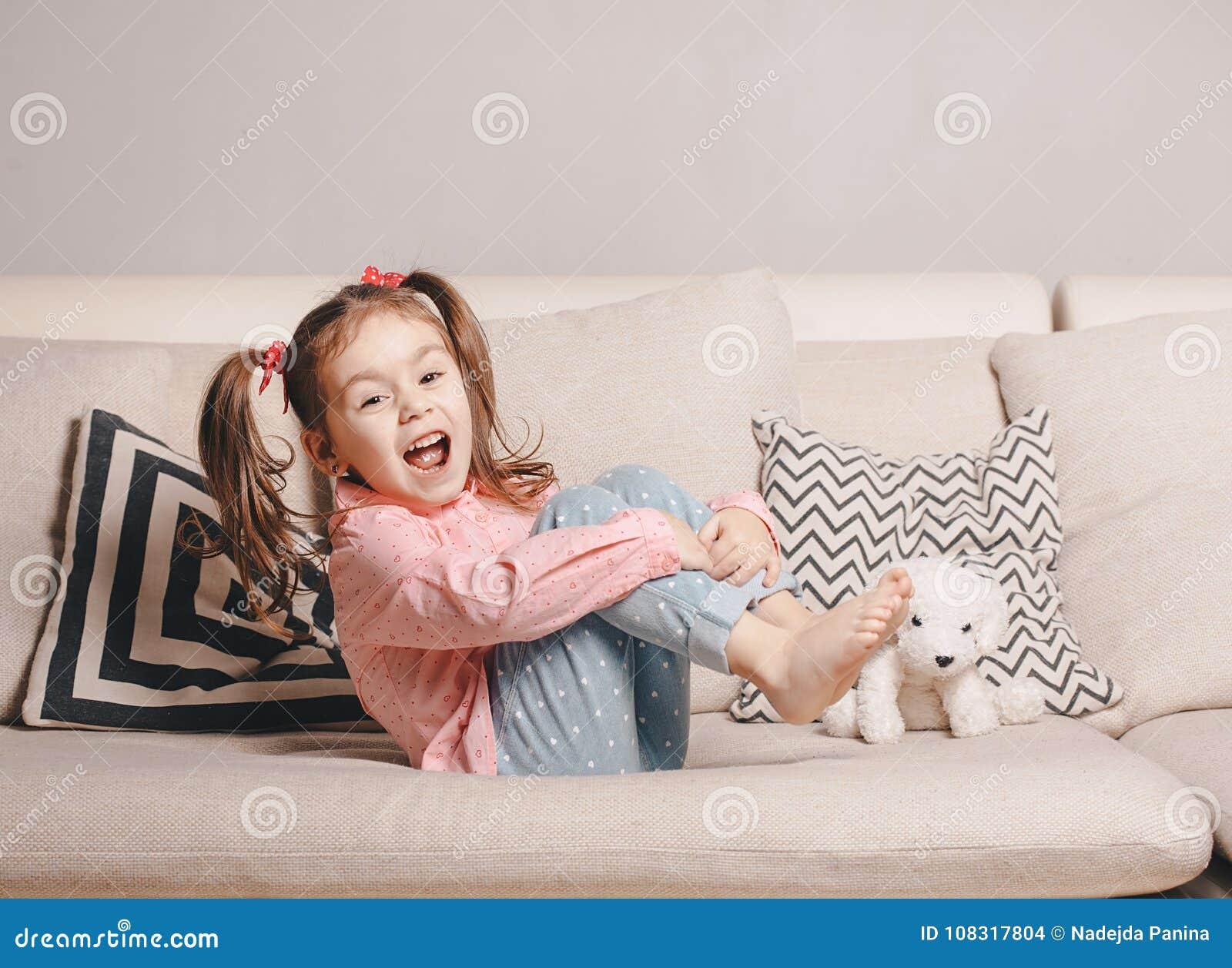Niña bastante feliz en sentarse que lleva casual en el sofá con el perro de juguete y la sonrisa