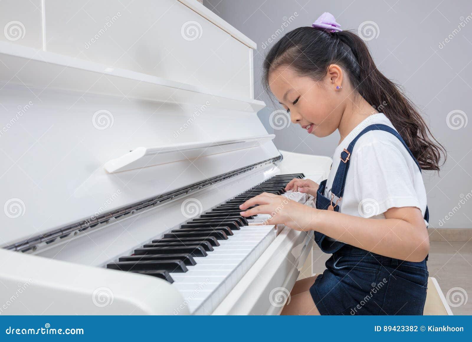 Niña china asiática feliz que juega el piano clásico en casa