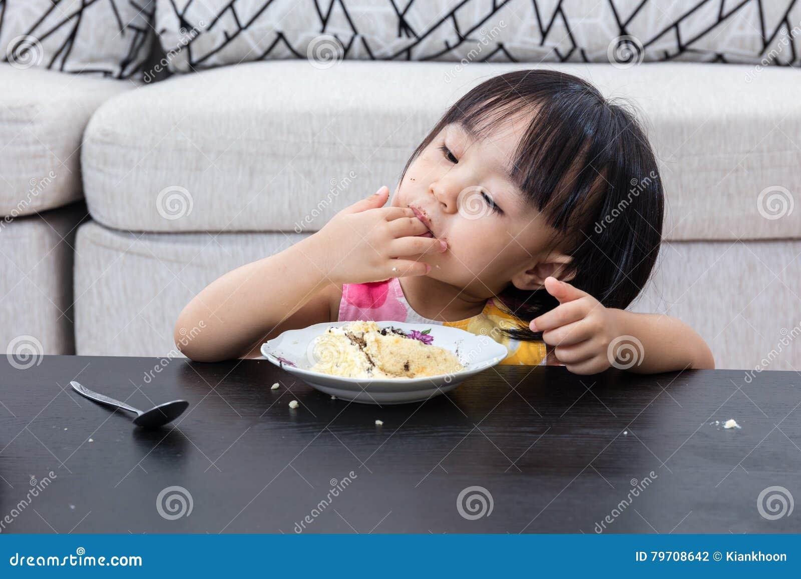 Niña china asiática que come el pastel de queso del cumpleaños
