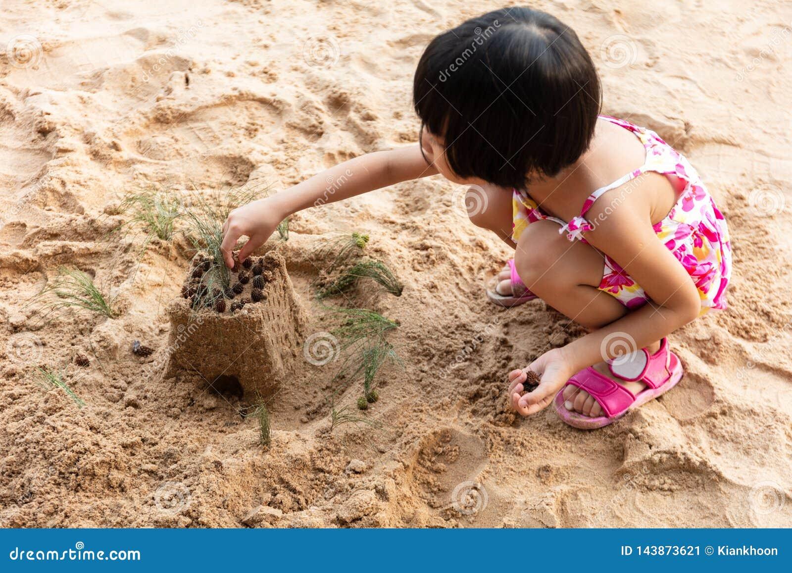 Niña china asiática que juega la arena en la playa