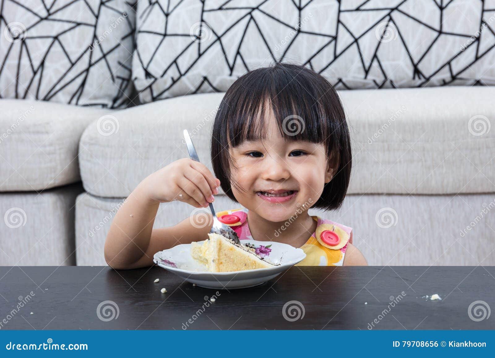 Niña china asiática sonriente que come el pastel de queso del cumpleaños
