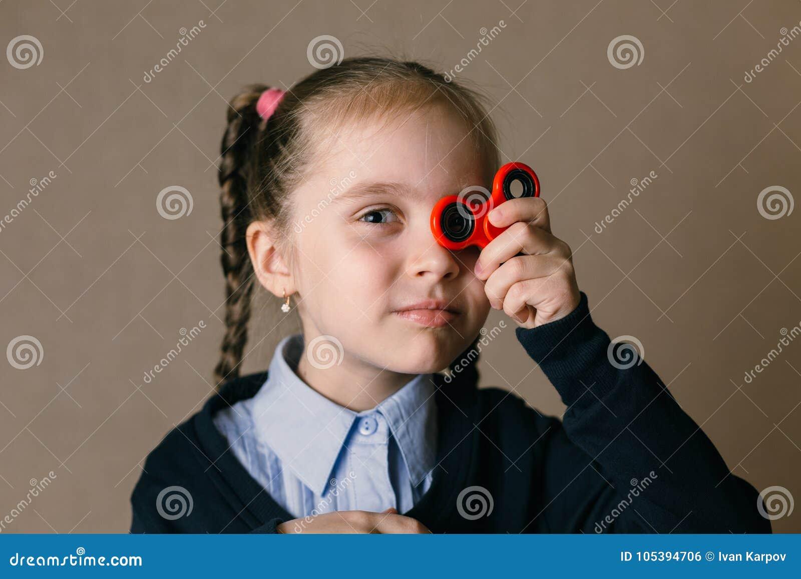 Niña con el hilandero de la persona agitada soportado a sus ojos