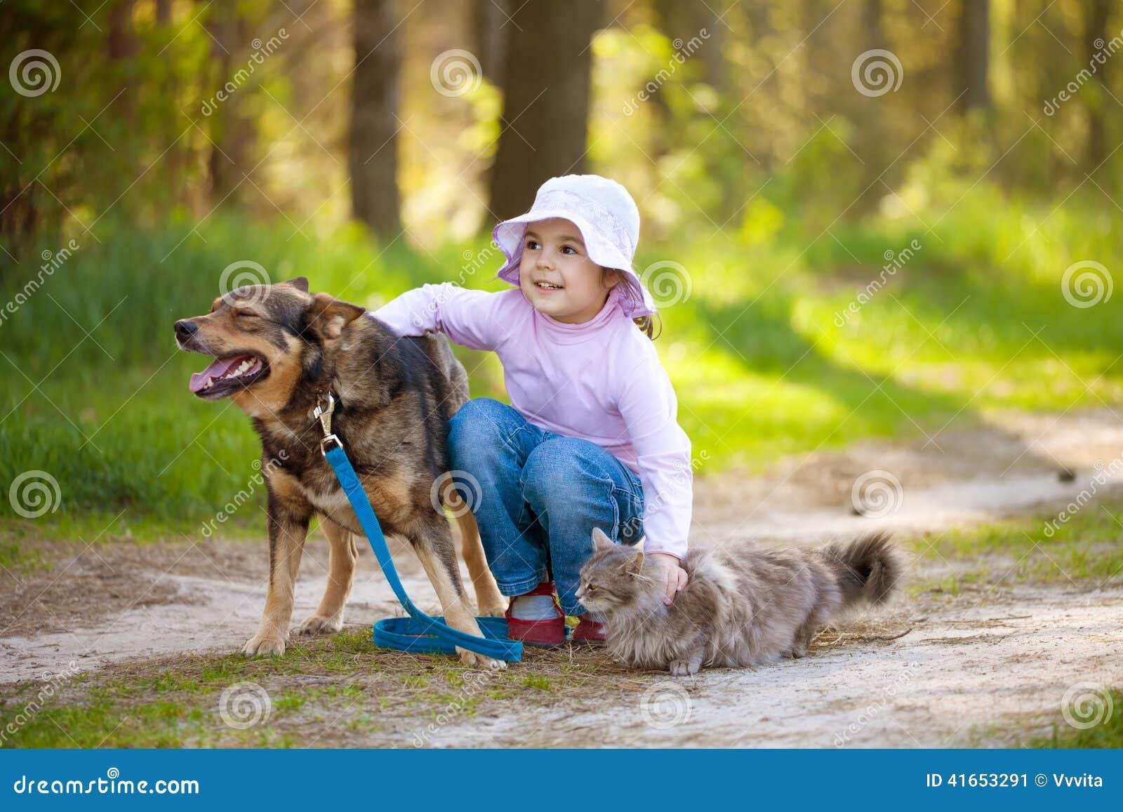 Niña con el perro y el gato grandes