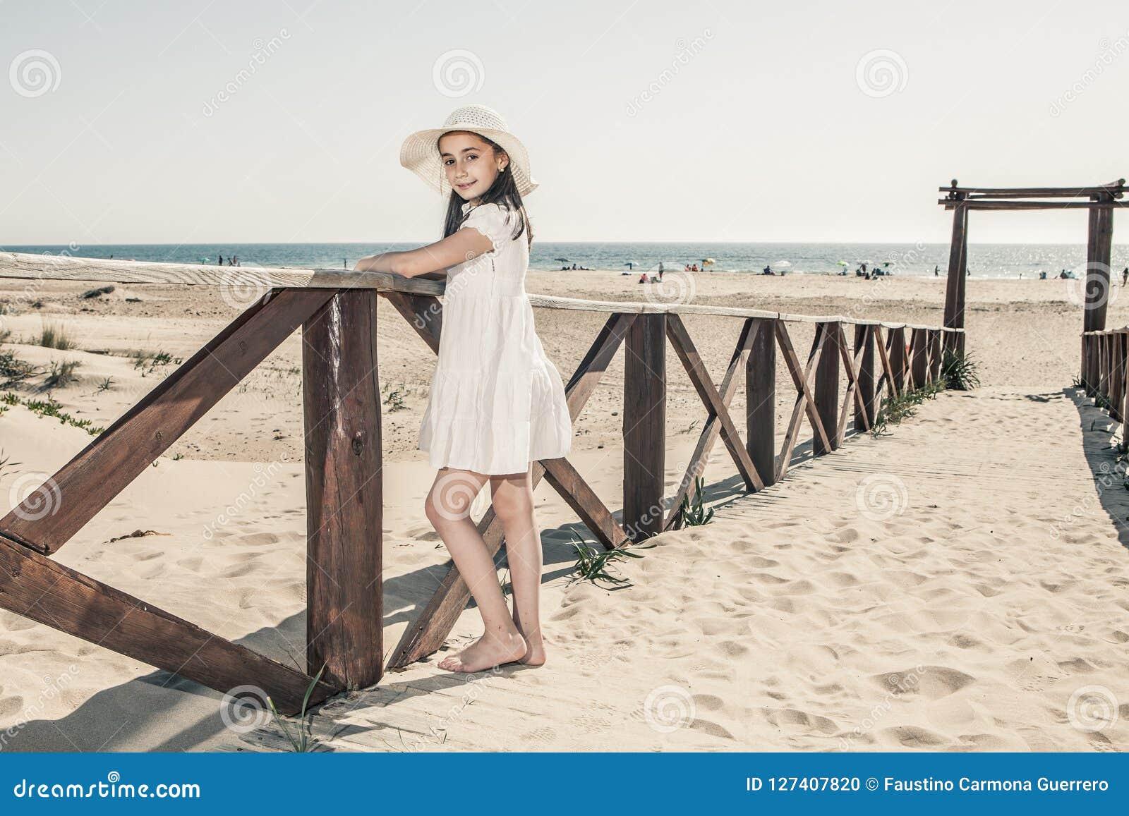 Niña con el sombrero que se inclina contra la verja de madera en la playa
