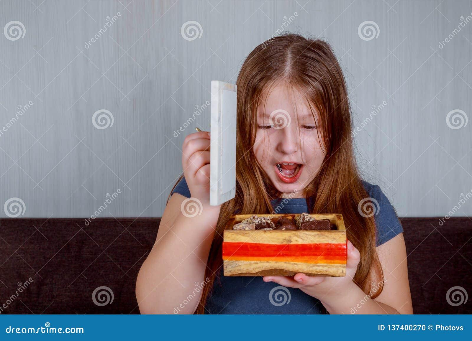 Niña con los caramelos en caja sorprendida sosteniendo un bastón de caramelo Feliz Navidad