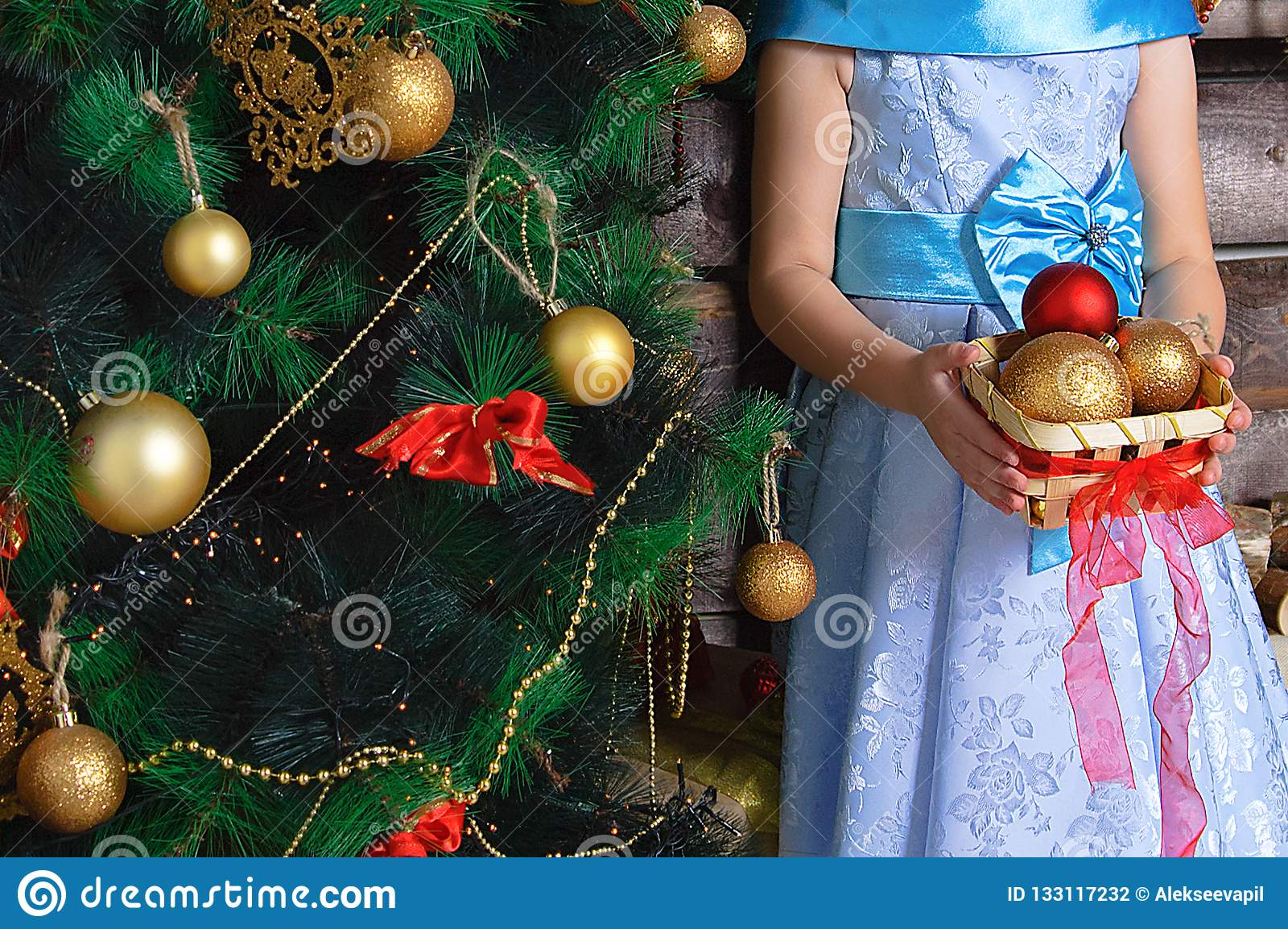 Niña Con Una Cesta De Decoraciones De La Navidad Se Coloca