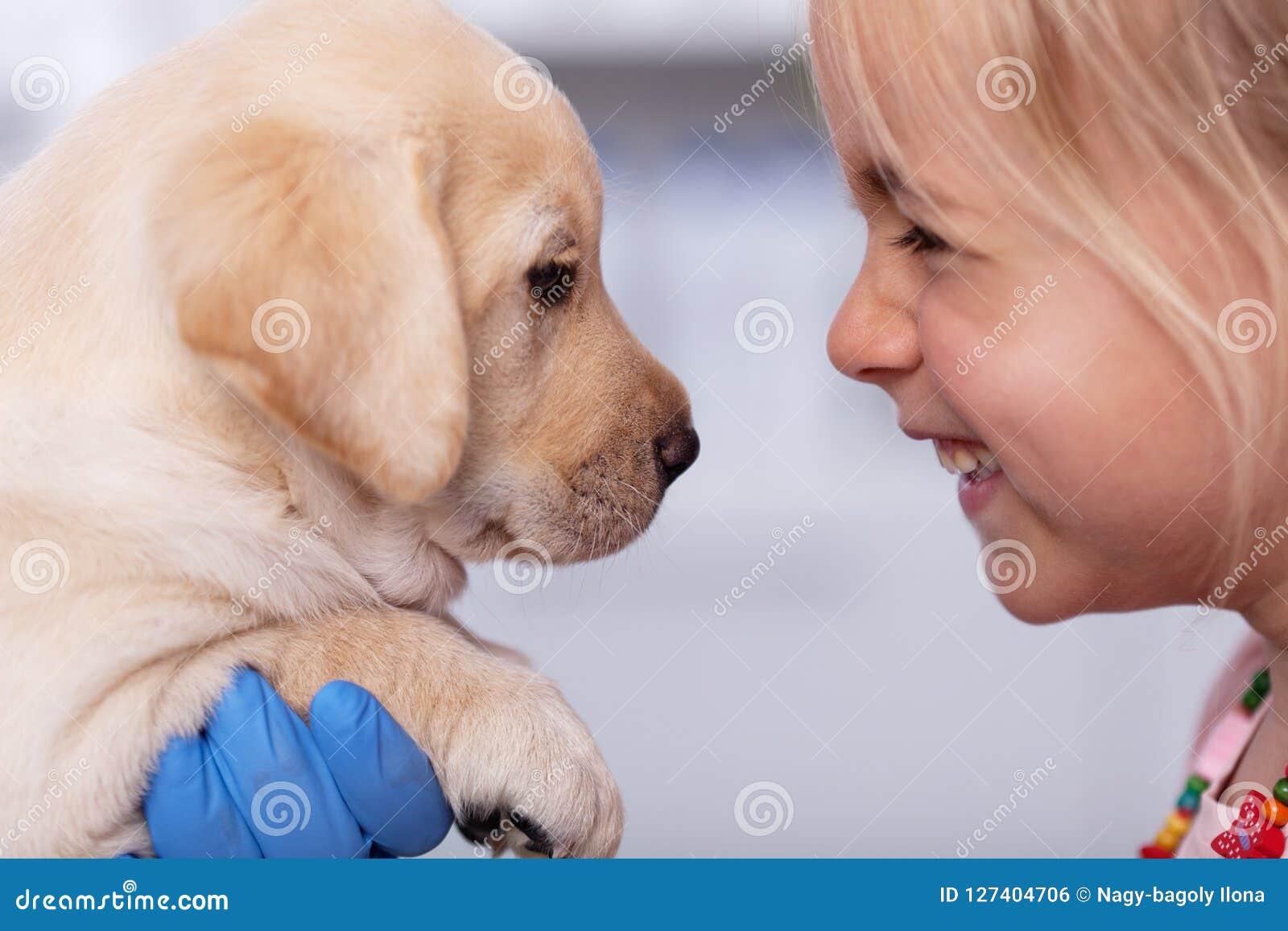 Niña con una sonrisa que encuentra su nuevo perrito en el refugio para animales