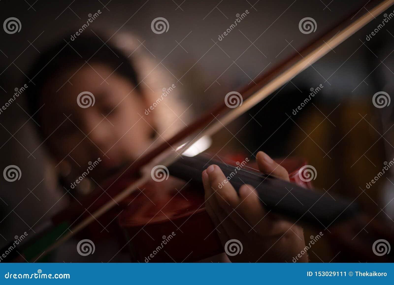 Niña del tiro del primer que juega a la orquesta del violín instrumental con el tono del vintage y la oscuridad y el grano del ef