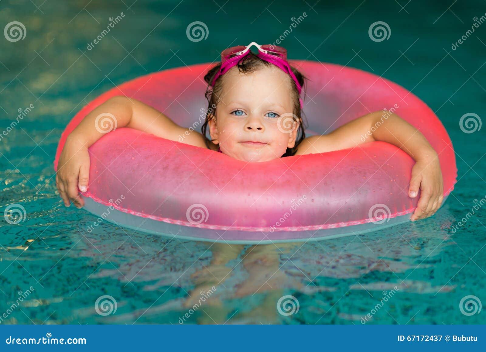 Niña divertida en gafas rosadas en la piscina