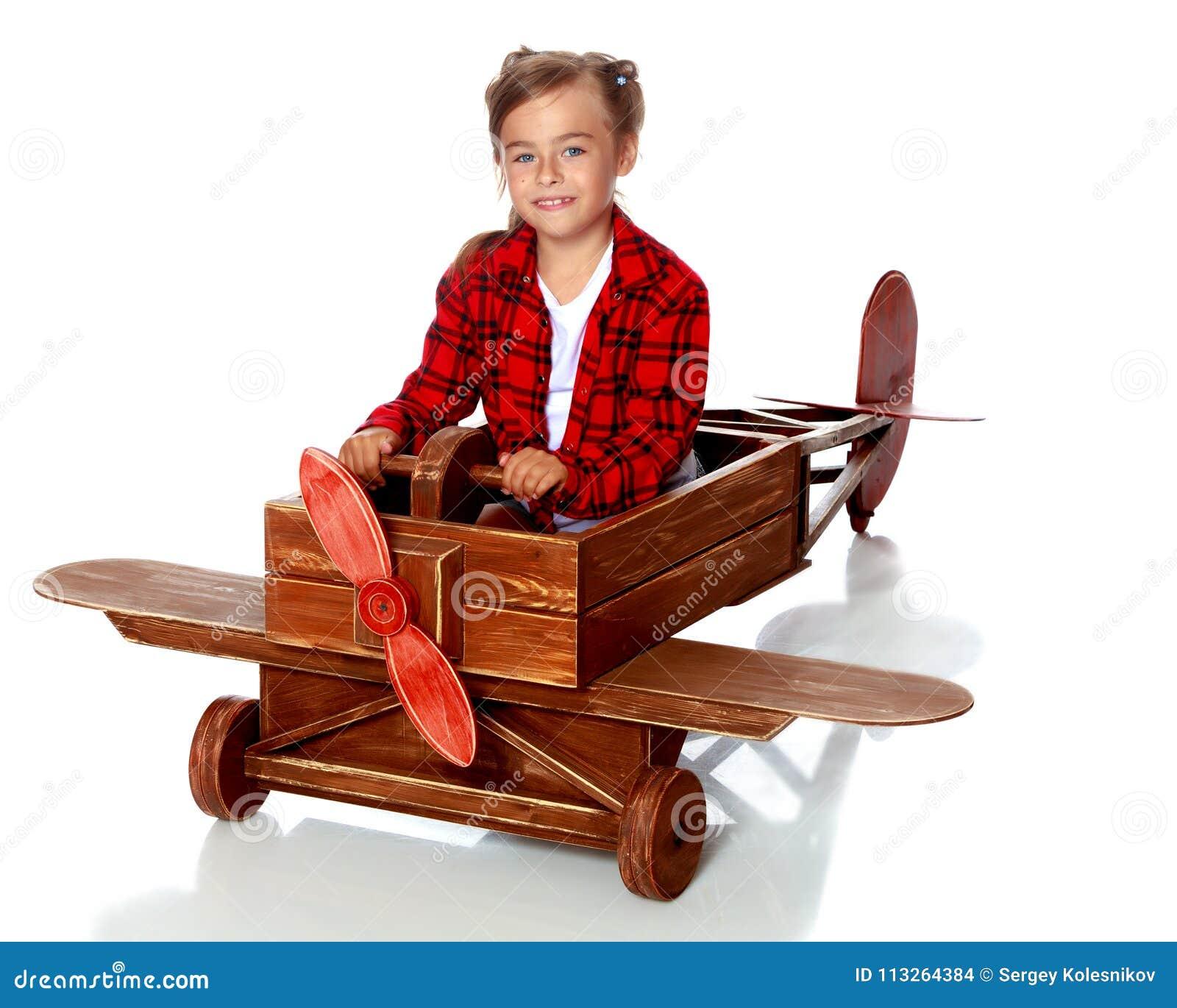 9ca935d5c4b1c Una niña en un casquillo experimental del ` s está jugando en un avión de  madera grande El concepto de una niñez feliz