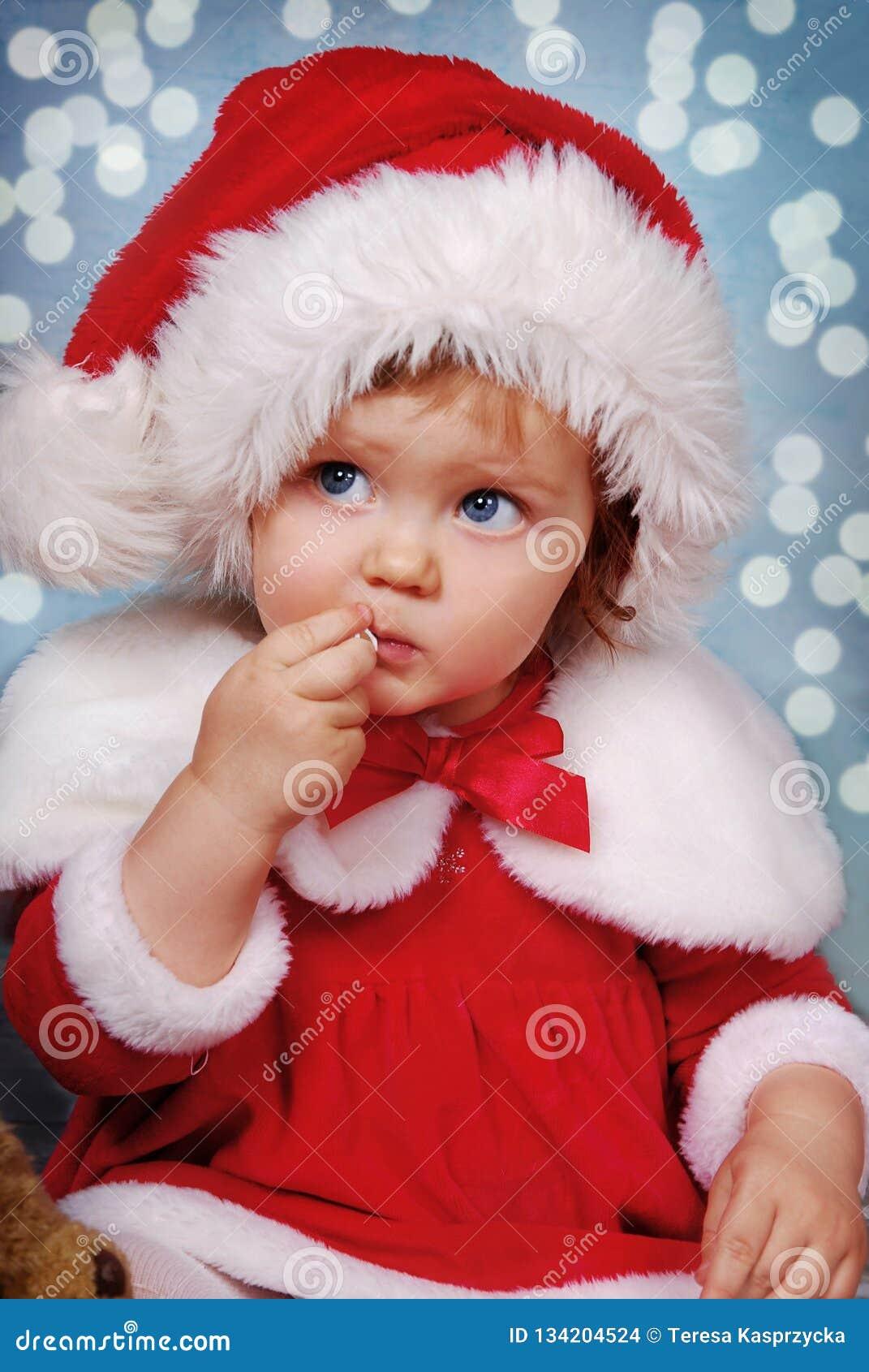 Niña en el sombrero de santa el tiempo de la Navidad