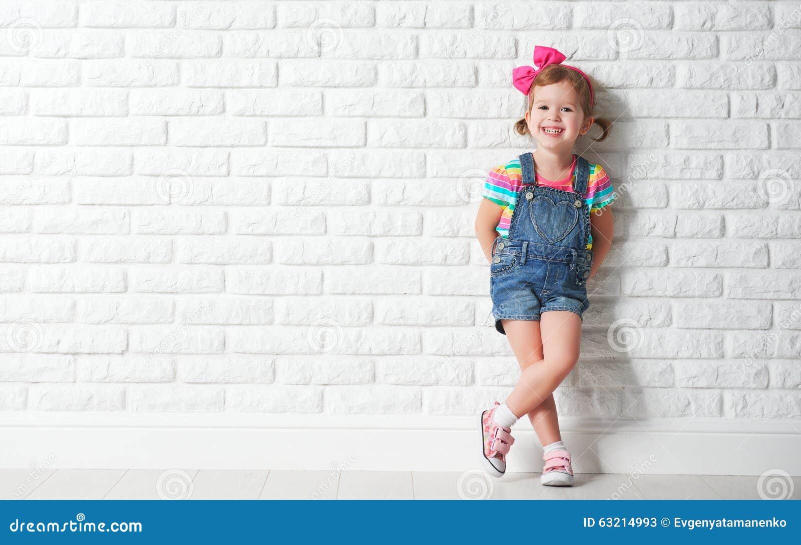 Niña feliz del niño que se ríe de la pared de ladrillo en blanco