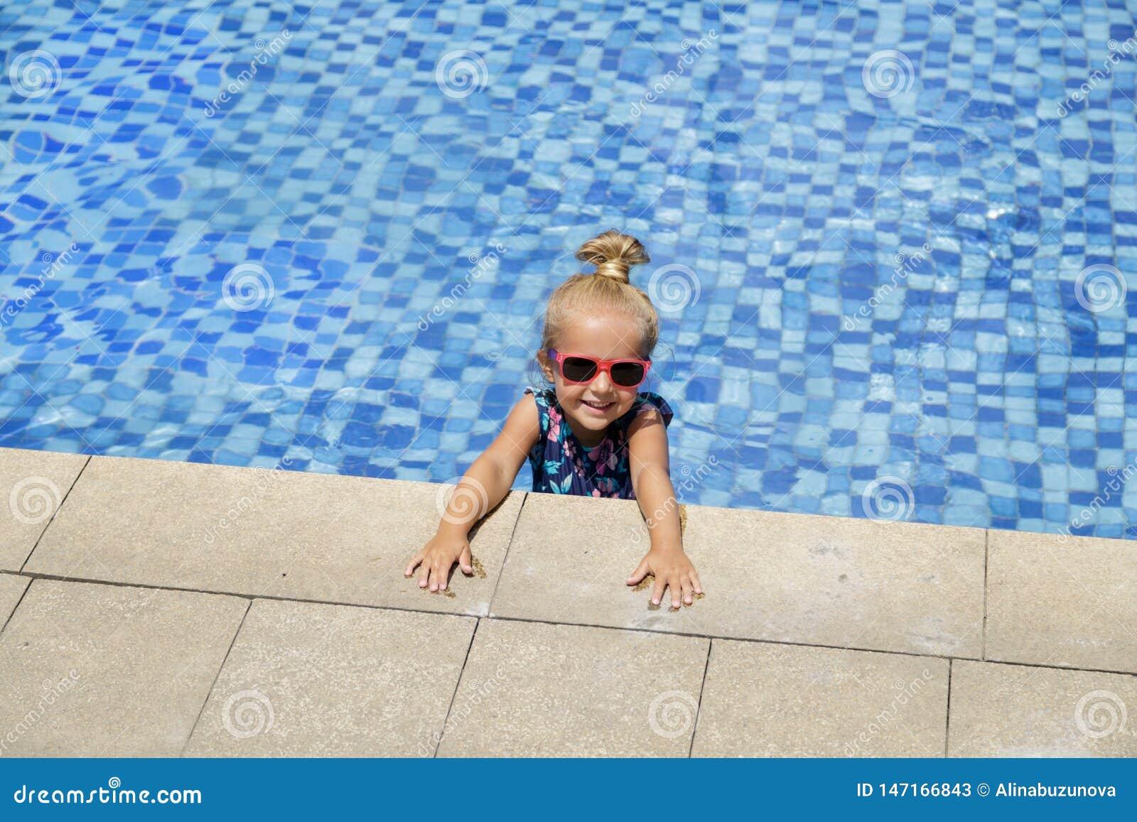 Niña feliz en piscina al aire libre en día de verano caliente Los ni?os aprenden nadar Juego de ni?os en centro tur?stico tropica
