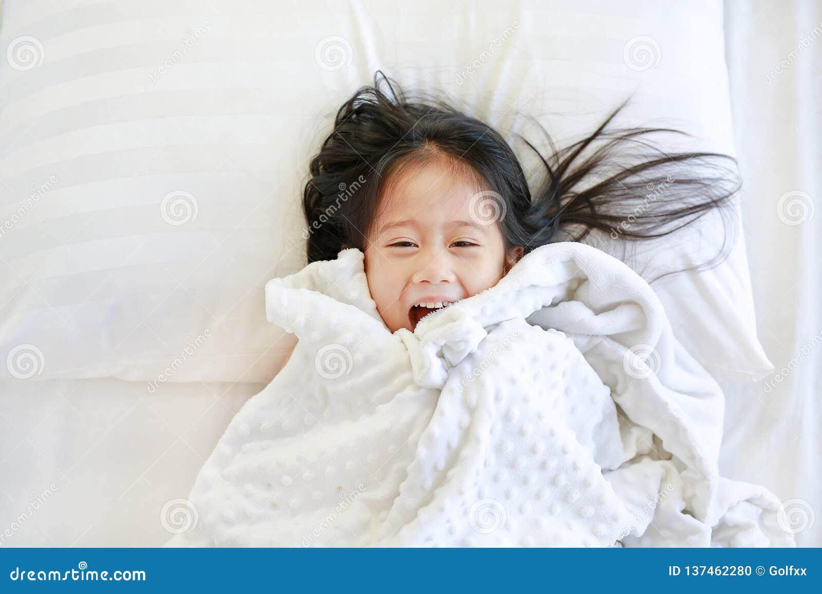 Niña feliz que miente en cama con la manta y que mira la cámara Visión superior