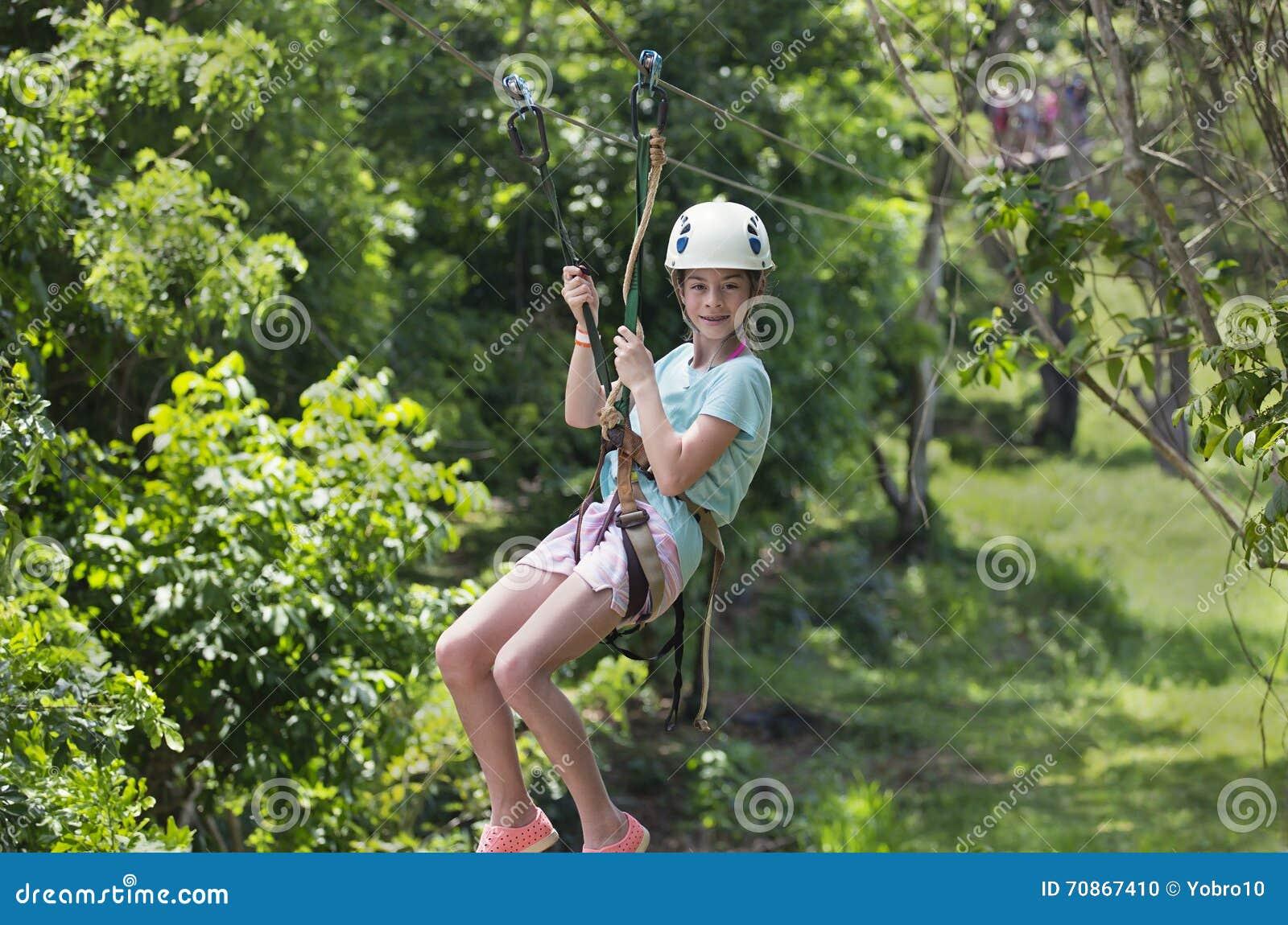Niña feliz que monta una línea de la cremallera en un bosque tropical enorme