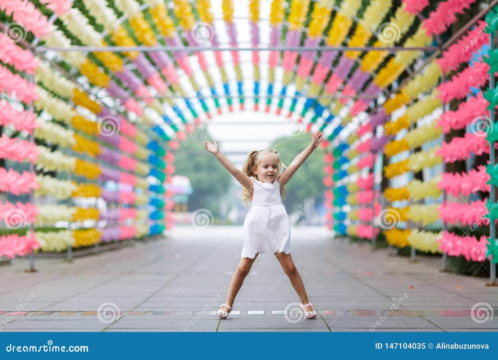 Niña feliz que salta y que se divierte en el callejón soleado brillante borroso del parque Concepto descuidado feliz de la ni?ez