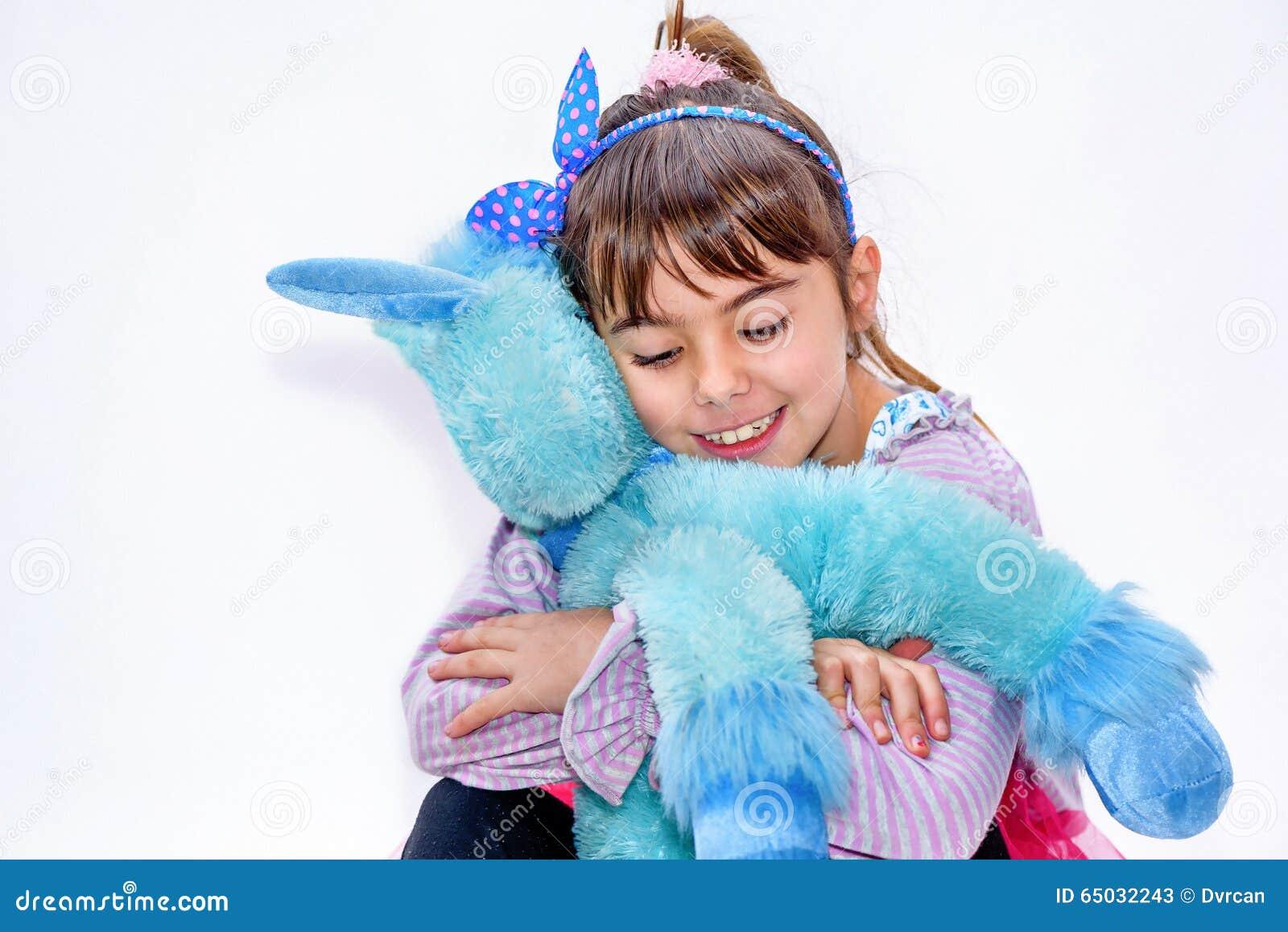Niña feliz que sostiene el juguete azul del unicornio aislado en blanco
