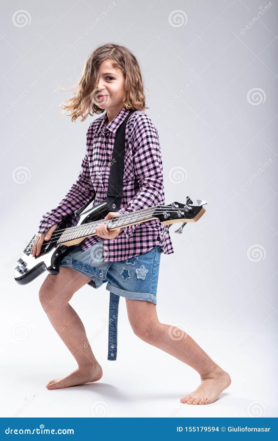Niña feliz sonriente que toca la guitarra eléctrica