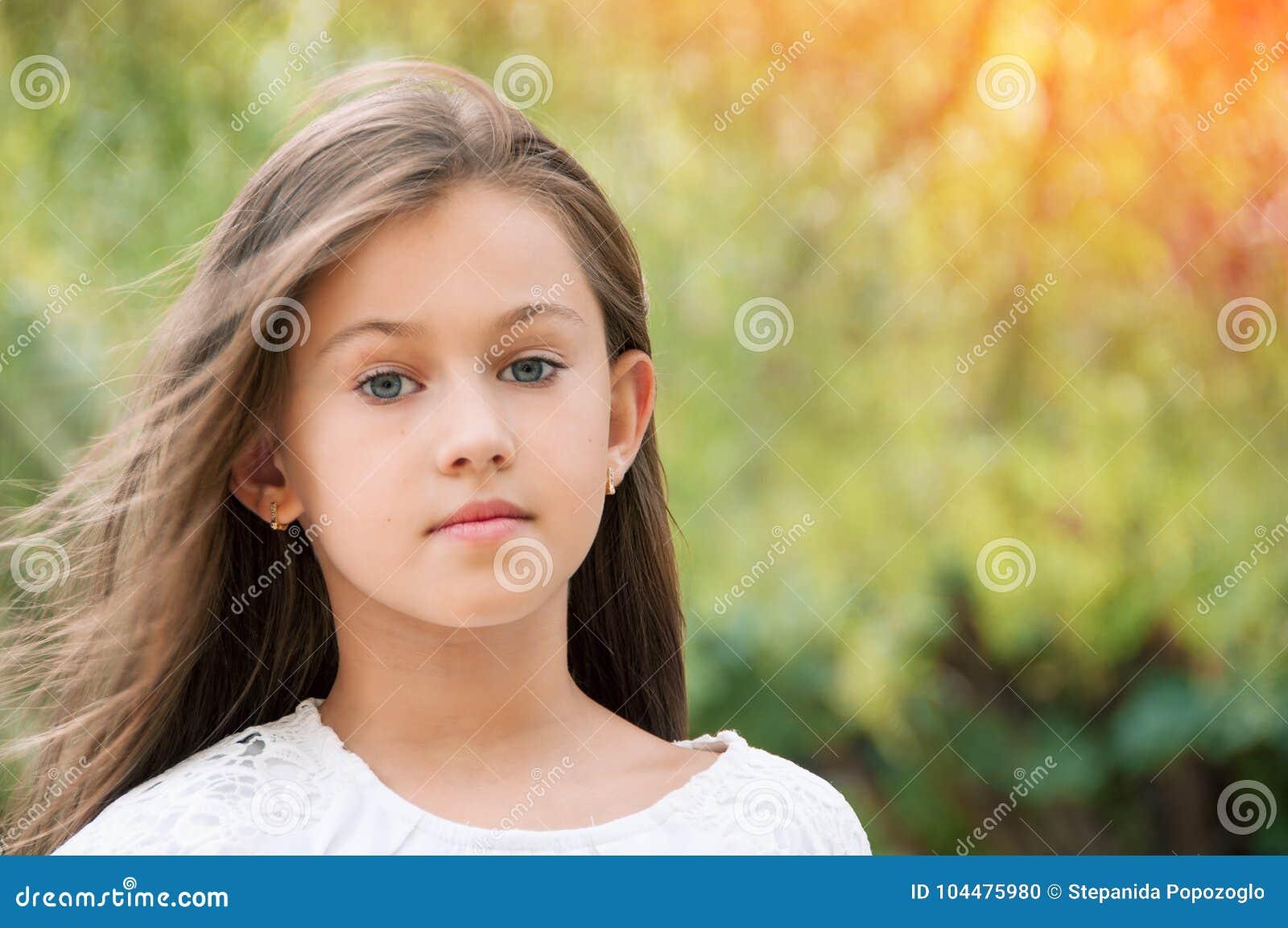 Niña hermosa en el parque, con el pelo largo y y un swee