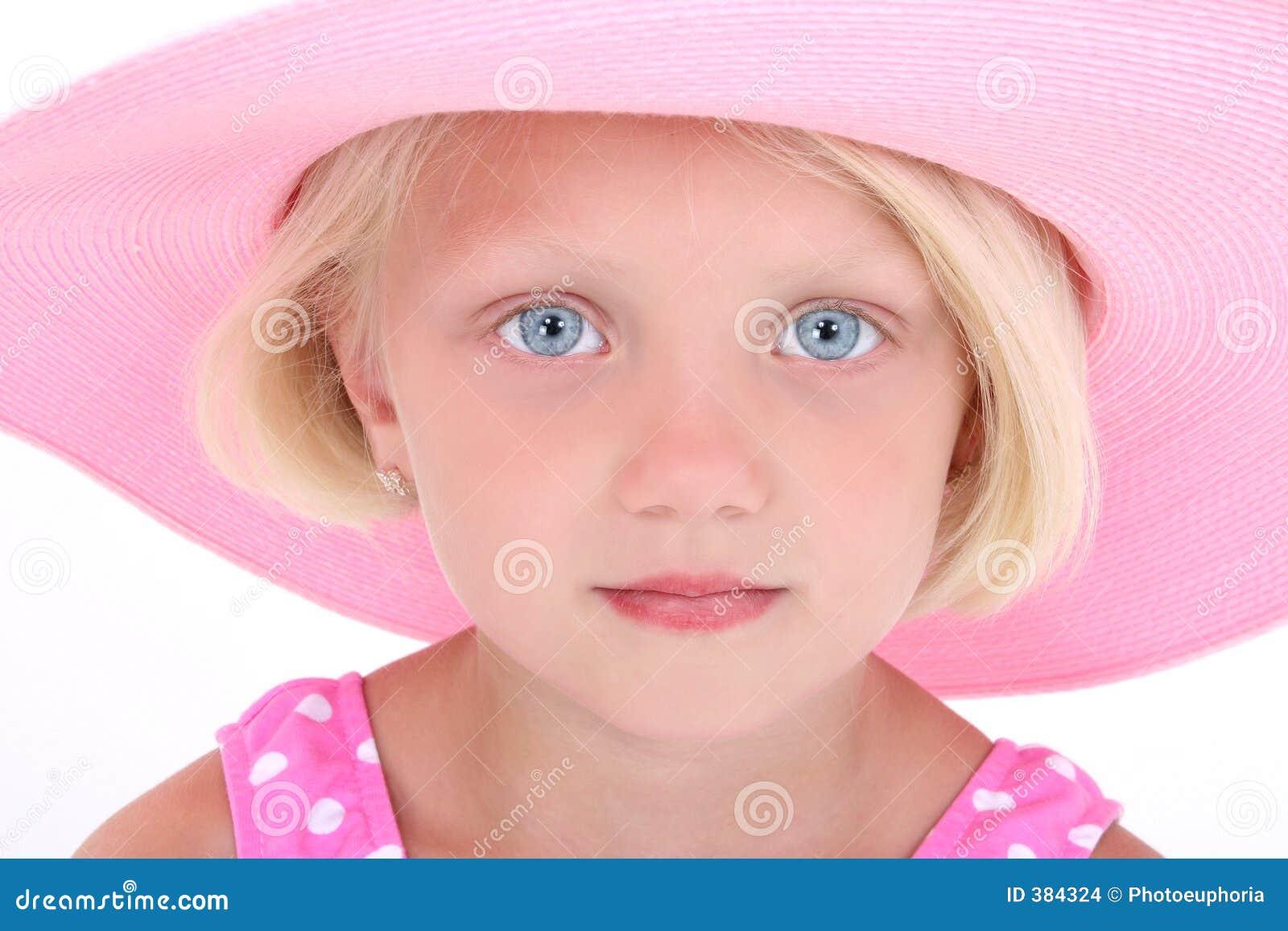 Niña hermosa en juego de nadada rosado y sombrero grande