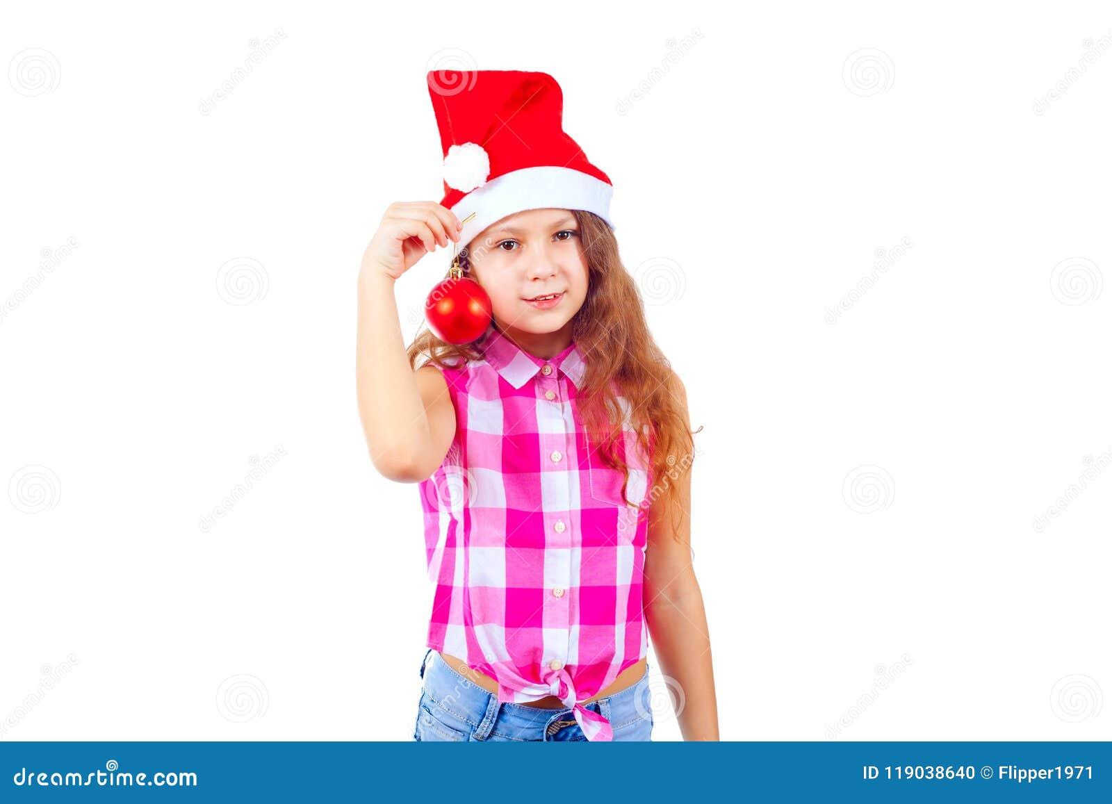 Niña linda en el sombrero de santa que lleva a cabo un juguete del árbol de navidad y un s